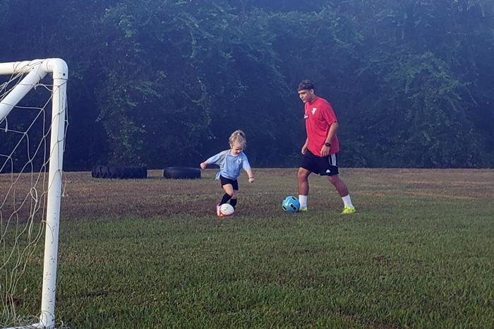 girl playing soccer with ymca coach