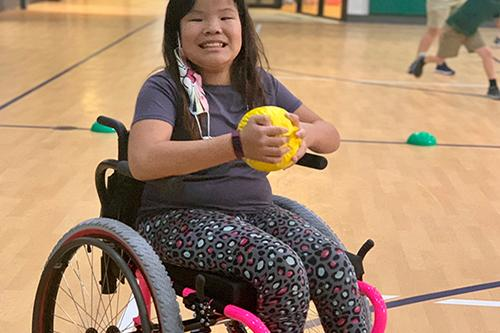 Young girl smiling in wheelchair, holding yellow ball in basketball gym