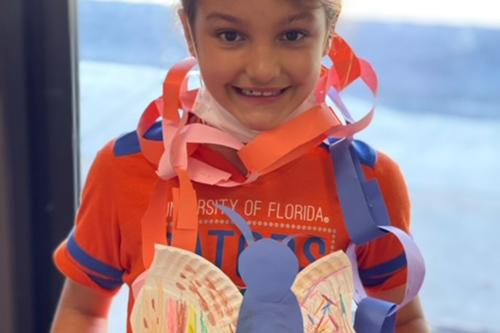 Young girl wearing handmade crafts from summer camp