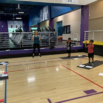 children standing on yoga mats in YMCA basketball gym