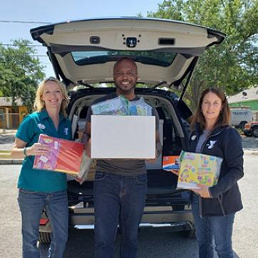 Tampa Y admin staff with Hillsborough Education Foundation staff holding school supplies