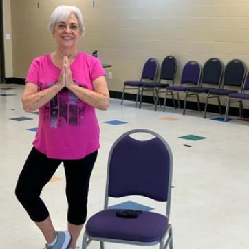 active older adult stands in tree pose by a chair at the ymca